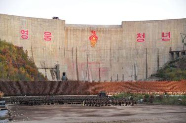 151004 - SK - KIM JONG UN - Ein großer Chor in Anwesenheit von Marschall KIM JONG UN - 01 - 백두산대국의 자랑스러운 청춘대기념비, 청년강국의 상징 백두산영웅청년발전소 훌륭히 완공 경애하는 김정은동지께서 발전소준공식에 참석하시여 력사적인 연설을 하시고 전체 건설자들과 함께 기념사진을 찍으시였다